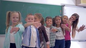 Groep basisschoolkinderen met jonge leraars golvende handen op achtergrond van bord in klaslokaal stock videobeelden