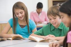 Groep basisschoolleerlingen het lezen stock foto's