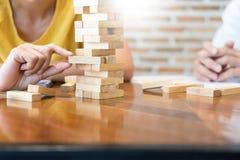Groep bedrijfs creatieve mensen die toren bouwen door houten blok stock fotografie