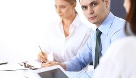 Groep bedrijfsmensen of advocaten die termijnen van transactie in bureau bespreken Collega's die allen samenwerken Nadruk o stock afbeelding