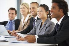 Groep Bedrijfsmensen die aan Collega luisteren die Bureauvergadering richten royalty-vrije stock foto