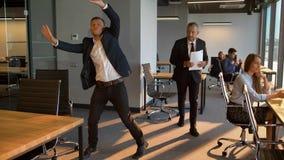 Groep bedrijfsmensen die dansende mannelijke collega bekijken, denken zij zijn gedrag vreemd is stock footage