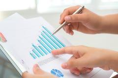 Groep bedrijfsmensen die op bedrijfsdocument richten tijdens Stock Foto's