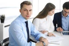 Groep bedrijfsmensen die vragen bespreken op vergadering in modern bureau Headshot van zakenman bij onderhandeling royalty-vrije stock afbeeldingen