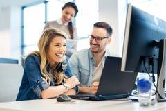 Groep bedrijfsmensen en softwareontwikkelaars die als groep in bureau werken stock afbeelding