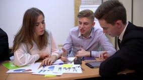Groep Bedrijfsmensen, Succesvol Team Discussing Reports 4 k-Commercieel team met documenten en laptop bij lijst stock video