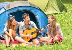 Groep beste vrienden die en pret zingen hebben die in openlucht kamperen Royalty-vrije Stock Foto
