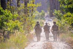 Groep bewapende militairen op de weg in bos Royalty-vrije Stock Afbeelding