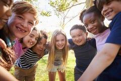 Groep binnen het glimlachen van schoolkinderenhelling aan camera het omhelzen royalty-vrije stock afbeeldingen