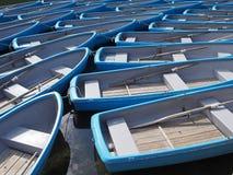 Groep blauwe roeiboot bij rivier stock fotografie