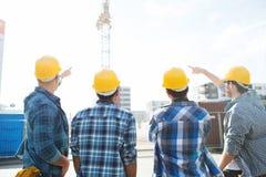 Groep bouwers in bouwvakkers bij bouwwerf royalty-vrije stock fotografie