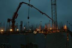 Groep bouwvakkers die aan een gebouw tijdens de nacht met een kraan op de achtergrond werken stock foto's