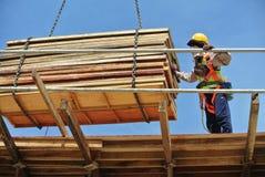 Groep bouwvakkers die bundel van hout opheffen die mobiele kraan met behulp van Stock Afbeelding