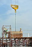 Groep bouwvakkers die bundel van hout opheffen die mobiele kraan met behulp van Royalty-vrije Stock Afbeelding