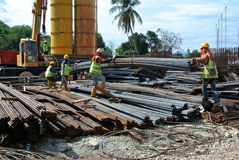 Groep bouwvakkers die bundel van versterkingsbar opheffen die mobiele kraan met behulp van Royalty-vrije Stock Foto
