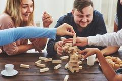 Groep creatieve vrienden die bij houten lijst zitten Mensen die pret hebben terwijl het spelen van raadsspel Stock Afbeelding