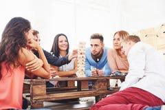 Groep creatieve vrienden die bij houten lijst zitten Mensen die pret hebben terwijl het spelen van raadsspel Stock Afbeeldingen