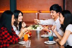Groep de Aziatische gelukkige en glimlachende jonge mens en vrouwen die een maaltijd samen met plezier en geluk hebben stock afbeeldingen