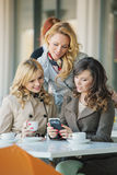 Groep de glimlachende vrouwen in de koffiewinkel royalty-vrije stock afbeeldingen