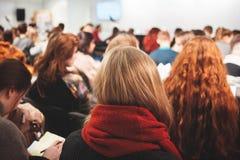 Groep de de jonge studentes en mensen die van vrouwenschoolmeisjes op het conferentie opleidingsonderwijs luisteren in het zaalkl stock afbeelding