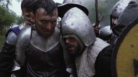 Groep de middeleeuwse militairen in pantser na de slag stock videobeelden