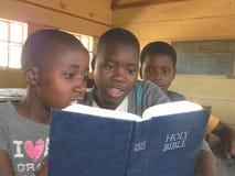Groep die Afrikaanse schooljonge geitjes Bijbel lezen Stock Foto