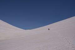 Groep die backpackers door het ravijn tussen twee snow-covered hellingen gaan Royalty-vrije Stock Foto's