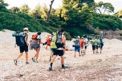 Groep die backpackers op een zandige weg langs de overzeese kust lopen stock afbeeldingen
