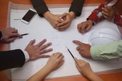Groep die bedrijfshanden een woonwijk in bureau schetsen, bedrijfsgroepswerkconcept stock afbeeldingen