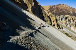 Groep die bergtrekkers op een steile rotsachtige heuvel in Himalayagebergte, Nepal lopen royalty-vrije stock afbeelding