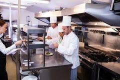 Groep die chef-kok voedsel in commerciële keuken voorbereiden Stock Afbeeldingen