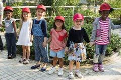 Groep die de schoolreizen van de jonge geitjesschool in openlucht botanisch park leren stock fotografie