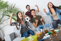 Groep die de ventilators van de vriendensport gelukkige op voetbalwedstrijd letten stock foto's