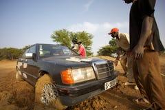 Groep die die mensen een auto in probleem helpen in de modder wordt geplakt Royalty-vrije Stock Foto's