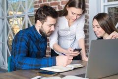 Groep die ervaren freelancers op video op celtelefoon letten tijdens het werkdag stock afbeelding