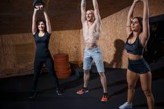 Groep die functionele fitness opleiding met kettlebell in sportgymnastiek hebben Royalty-vrije Stock Foto's
