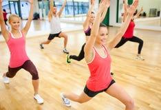 Groep die glimlachende mensen zich in de gymnastiek uitrekken Stock Afbeelding