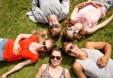 Groep die glimlachende vrienden op gras in openlucht liggen Stock Afbeeldingen