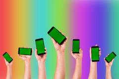 groep die handen op Smartphones tegen kleurrijke achtergrond opheffen - Handen die telefoons houden stock fotografie