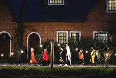 Groep die jonge geitjes met Halloween-kostuums aan truc of het behandelen lopen stock foto's