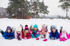 Groep die jonge geitjes op het ijs liggen stock foto