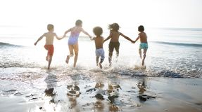 Groep die jonge geitjes van hun tijd genieten bij het strand stock foto's