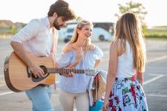 Groep die jonge toeristen die pret hebben en gitaar in een parkeerterrein spelen, op vervoer wachten royalty-vrije stock fotografie