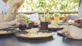 Groep die jonge vrienden die van een maaltijd genieten, pizza eten stock footage