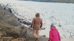 Groep die jongeren die in de Vatnajokull-ijslagune lopen, in de bergen wandelen samen om de gletsjers te zien stock footage