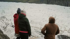 Groep die jongeren die zich op de berg bevinden en aan iets tonen, in Vatnajokull-ijslagune lopen in IJsland stock video