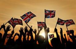 Groep die Mensen Britse Vlaggen in Achterlit golven Royalty-vrije Stock Foto's