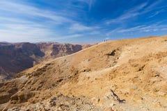 Groep die mensen de helling van de woestijnberg stijgen stock afbeelding