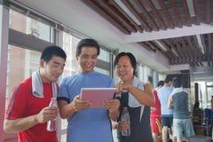 groep die mensen digitale tablet in de gymnastiek bekijken Royalty-vrije Stock Foto's