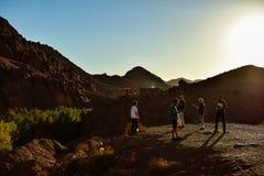 Groep die mensen een foto voor een berg proberen te nemen Stock Afbeelding